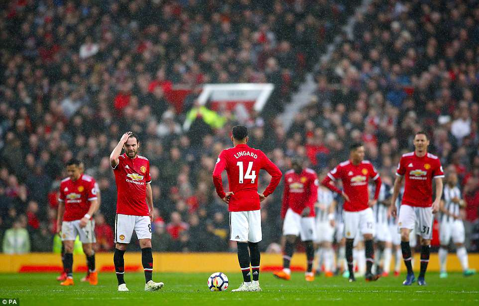The Manchester United players look dejected as Juan Mata and Jesse Lingard prepare to restart the match after the goal