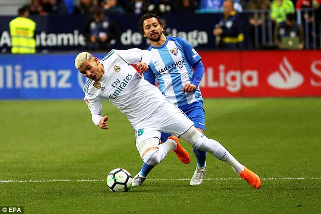 Young defender Theo Hernandez goes down under the challenge fromManuel Iturra