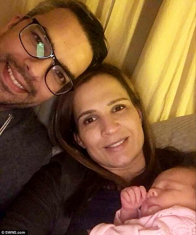 Kare Geraghty, 34, from Leicester, noticed swelling under her left ear when she went into labour in hospital - but doctors stressed it was nothing to worry about (pictured with her partner, Paul Dhillon, and baby Ivy)