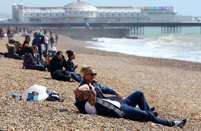 Flocks of people took to the beach in Brighton as African weather made its way across Britain today