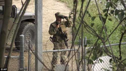 A National Guard troop watches over Rio Grande River on the border in Roma, Texas on Wednesday. The deployment of National Guard members to the U.S.-Mexico border at President Donald Trump's request was underway Tuesday with a gradual ramp-up of troops under orders to help curb illegal immigration