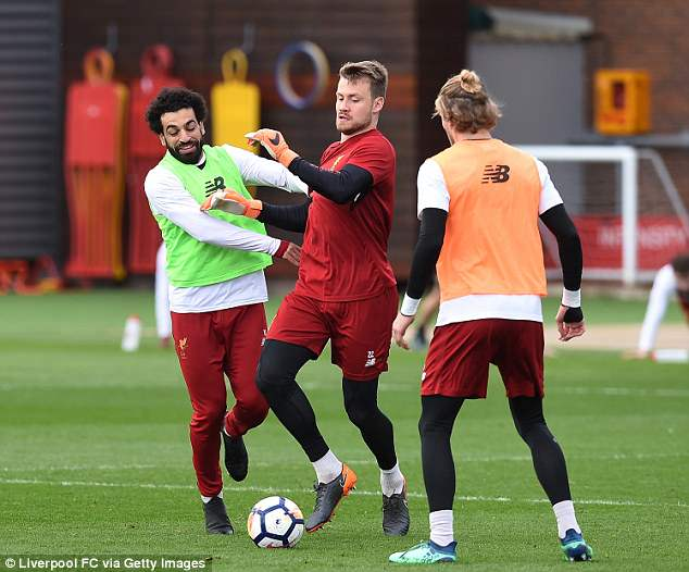 Simon Mignolet and Salah challenge for the ball during a training session on Tuesday