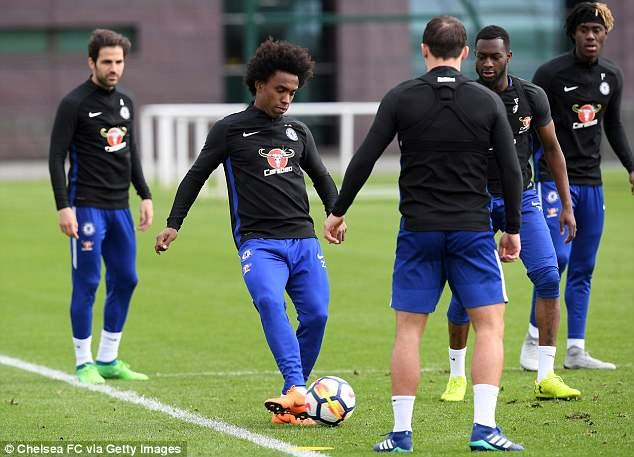 Brazilian forward Willian plays a pass during the Blues' practice at their Cobham base