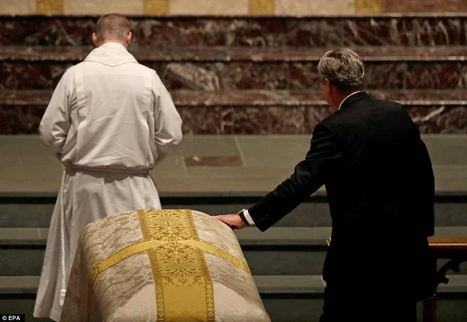 One last goodbye: Jeb places a hand on his mother's casket as he heads up to deliver his eulogy on Saturday
