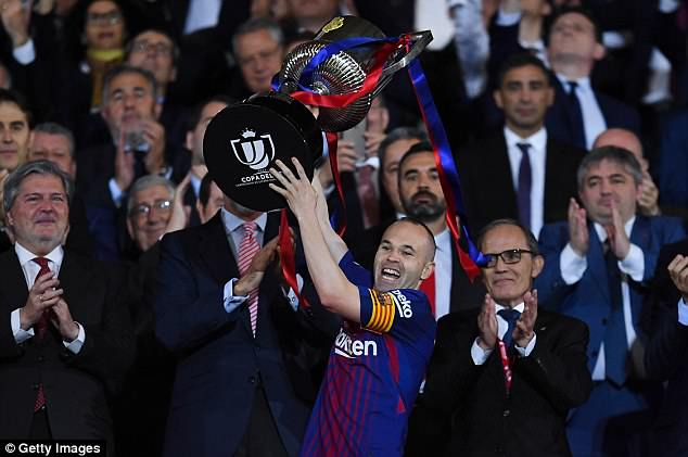 Lionel Messi enabled Iniesta to lift the trophy following the victory over Sevill