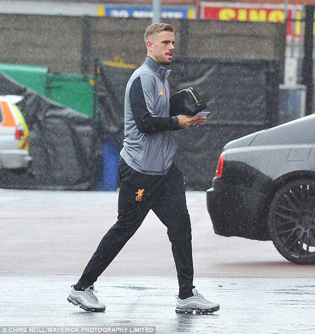 Liverpool captain Jordan Henderson heads off to the team's hotel on a rainy Tuesday afternoon