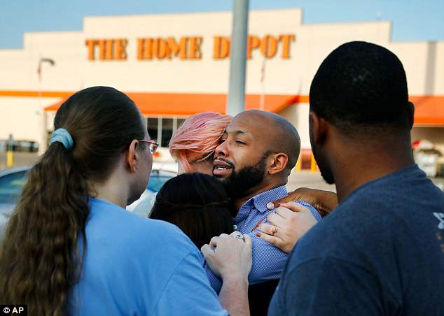 Home Depot employees comfort one another outside the store in Dallas following the shooting on Tuesday