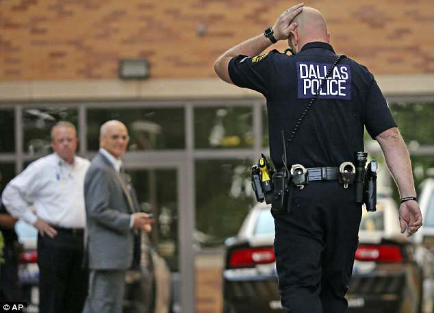 A Dallas Police officer walks towards Presbyterian Hospital on Tuesday where the three victims are being treated