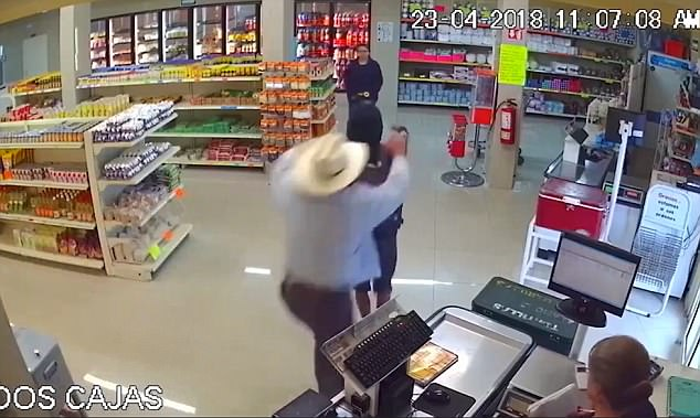 The mugger then points the gun at the hero, who is wearing a beige cowboy hat with denim biker coat, before turning away to threaten the shoppers in the store