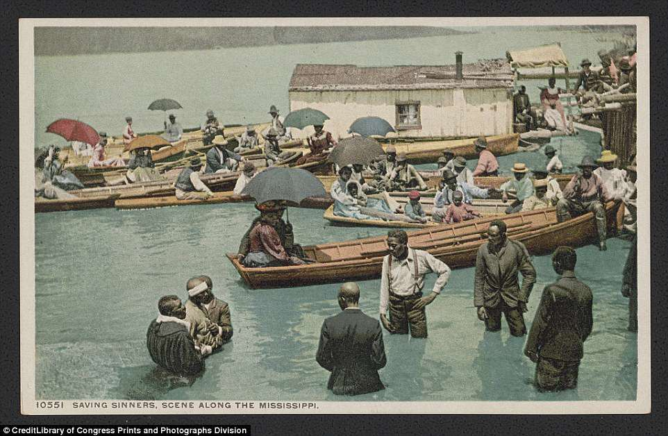This photograph from circa 1912 shows a baptism of African American men in the Mississippi with onlookers in rowboats