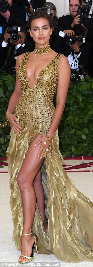 The leggy Lions Model flaunted her fit 5ft10in figure in a plunging embellished gown featuring a feather-like train and matching choker and stilettos