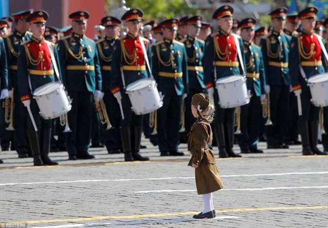 軍隊の赤い広場の前に軍隊の少女が立っています