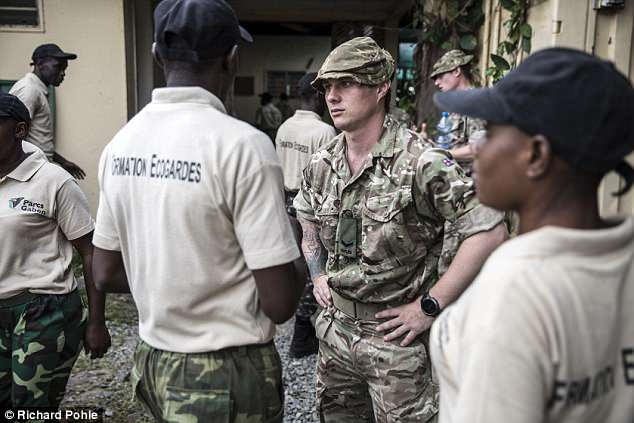 A British rifleman from the 2nd battalion The Rifles regiment has a quiet word with a National park ranger from Gabon before they head out for an exercise