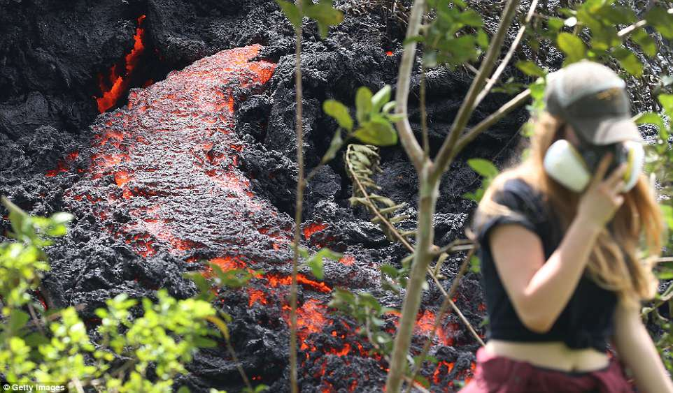 Kilauea, on Hawaii's Big Island, is threatening to blow its top in the coming days or weeks, after a week of sputtering lava and forcing about 2,000 people to evacuate. Above a resident is seen near the lava Saturday