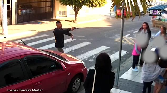 The robber, dressed in a black jacket, was seen on a security camera approaching a private school in Sao Paulo before aiming a gun at terrified mothers