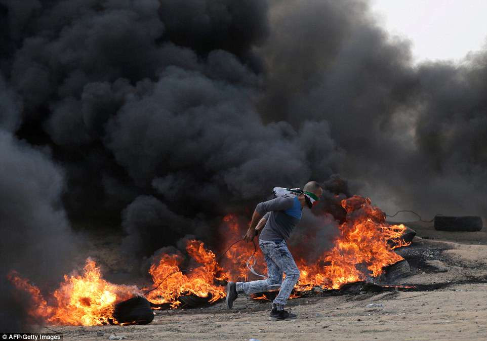 The US moved its embassy in Israel to Jerusalem today after months of global outcry, Palestinian anger and exuberant praise from Israelis. Israeli snipers killed a Palestinian man as protests got underway this morning. Pictured: A protester running past burning tyres