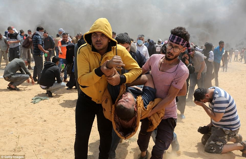 Palestinians carry an injured protestors to safety as one man kneels on the ground holding his head as violence erupted on the Gaza strip today