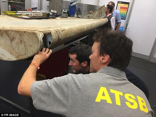 Mike Keane, a former easyJet chief pilot and Royal Air Force intelligence officer, said the ATSB (pictured examining MH370 debris) should change its 'ghost flight' theory of what happened to the missing jet