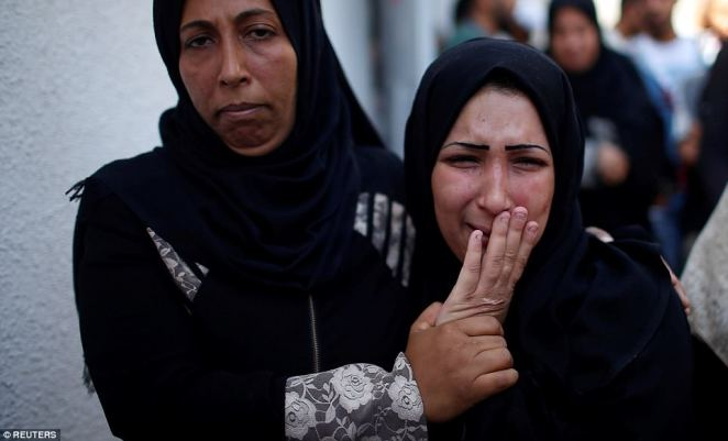 The mother of the eight-month-old Palestinian baby is comforted as she weeps during her daughter's funeral in Gaza City today