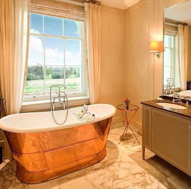Rooms come with giant bath tubs with views of the rolling countryside, including this grand copper roll top