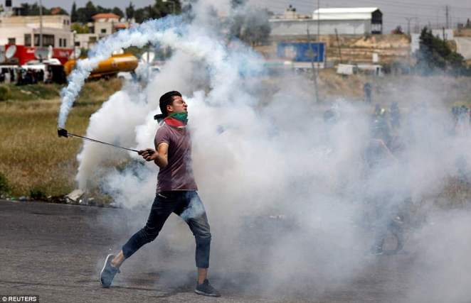 This Palestinian protester used a sling shot to hurl back a tear gas canister after it was launched towards him by Israeli troops