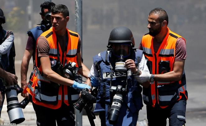 Caught in the crossfire: Medics escort a wounded photojournalist from the conflict zone in Bethlehem, West Bank