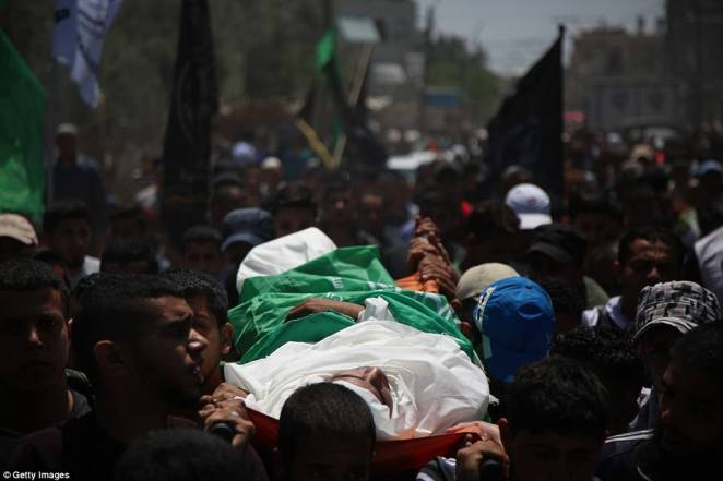 Palestinian mourners carry the dead body of Mukhtar Ebu Hamas, 25, who was killed during clashes in Gaza on Monday