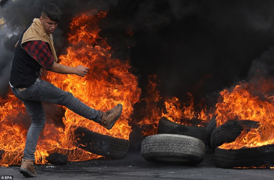 A Palestinian demonstrator kicks burning tires, during clashes with Israeli troops at a checkpoint near Nablus
