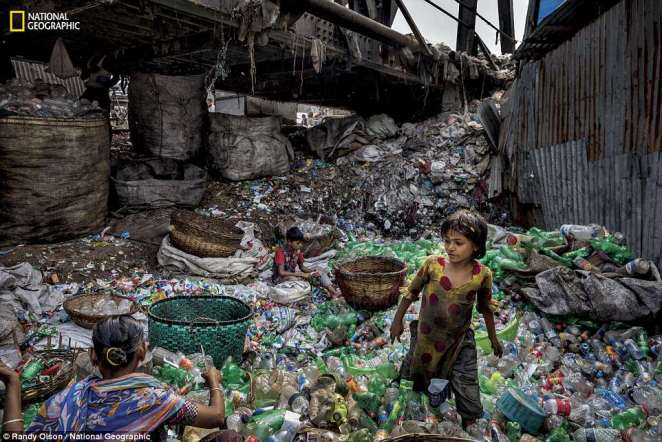 Under a bridge on a branch of the Buriganga River in Bangladesh, a family removes labels from plastic bottles, sorting green from clear ones to sell to a scrap dealer- where waste pickers can earn around $100 a month