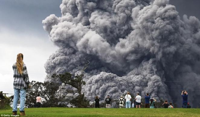 People watch at a golf course as an ash plume rises in the distance from the Kilauea volcano on Hawaii's Big Island as the USGS announces a major, explosive eruption is imminent