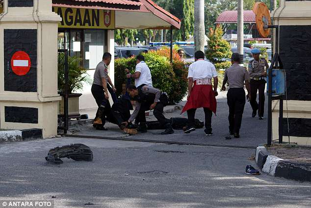 Police remove the bodies of attackers who were shot and killed at the entrance of the station   (pictured)