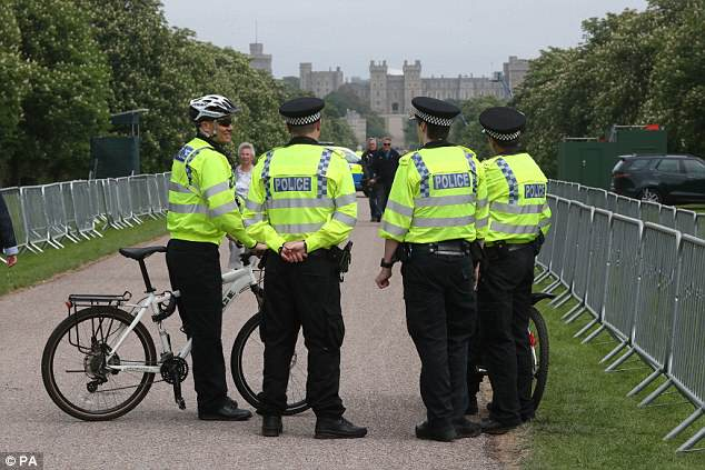 Police officers stand today outside Windsor Castle on the Long Walk in the Berkshire town
