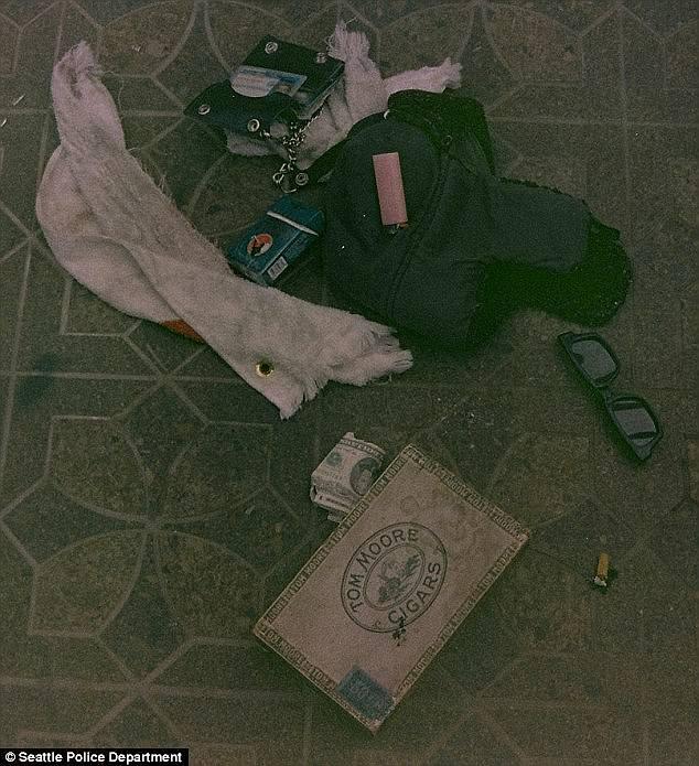A box of drug paraphernalia alongside his glasses, a wallet, lighter, cigarette butt, cash, and a pack of cigarettes
