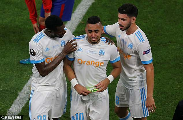 The Marseille captain is consoled by his Marseille team-mates as he leaves the field early