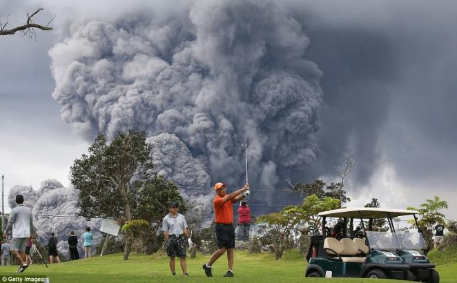 A group of golfers were seen playing a round nearby Hawaii's Kilauea volcano, which has been erupting for 11 days, as an ash cloud forms behind them