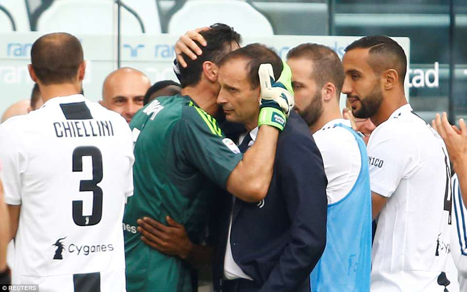 Buffon hugs his Juventus manager Massimiliano Allegri after returning to the bench to warm applause from the players
