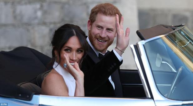 Harry and Meghan waved as they drove to Frogmore House in a converted electric car for their reception