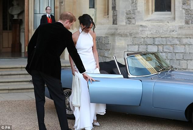 Harry helped his new wife, who was wearing a flowing Stella McCartney gown, into the car, as she held the long dress