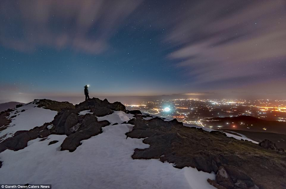 Mr Owen looks out over the bright lights of a town while standing on top of Elidir Fawr in Snowdonia