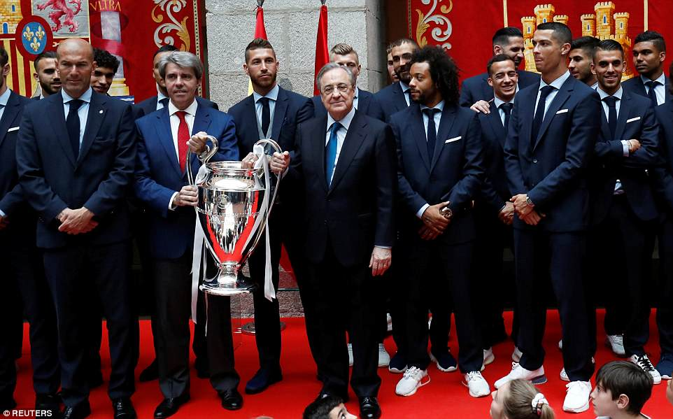 The victorious Spanish giants line up for a photo with the Champions League trophy at their parade on the weekend