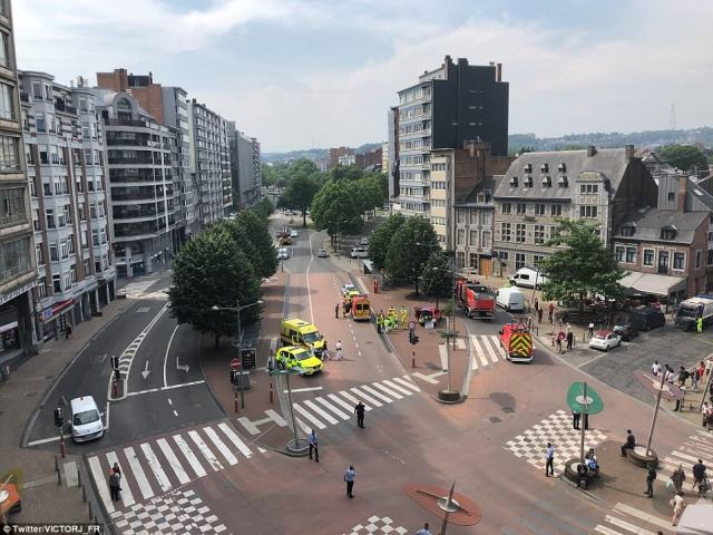 Scene: A witness' photo show emergency services in central Liege after the unnamed man shot two police officers and a bystander, and then took a woman hostage inside a high school