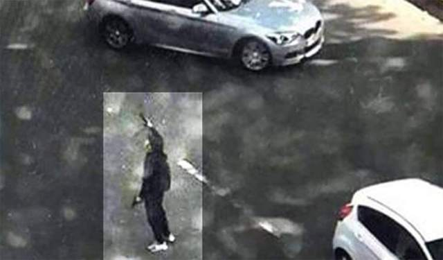 Attacker: This image published by Belgian news website HLN allegedly shows the male attacker brandishing two firearms which he reportedly stole from the policewomen he gunned down in Liege, Belgium