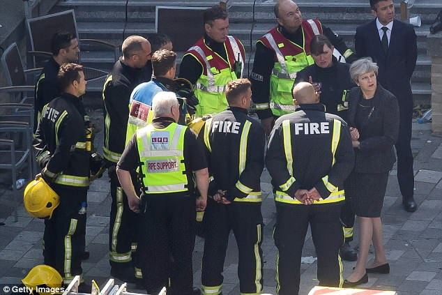 Pictured: Theresa May speaks to Dany Cotton, Commissioner of the London Fire Brigade as she visits Grenfell Tower, on June 15, 2017