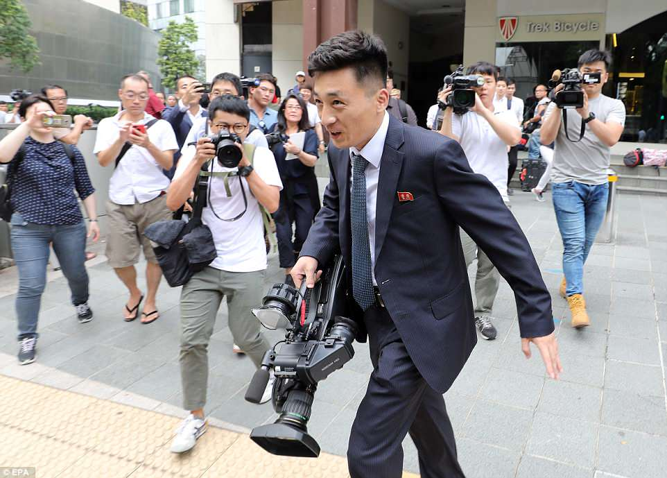 A North Korean reporter is chased by a group of Western reporters as he appears at the media center at the Formula One racing track in Marina Bay, Singapore on Sunday ahead of Trump's summit with Kim on June 12