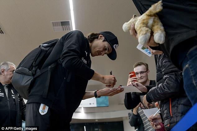 Edinson Cavani signsautographs for fans as he arrives with his international team-mates