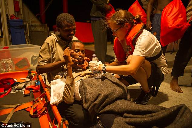 Treatment: An aid worker helps a migrant from Senegal on the boat