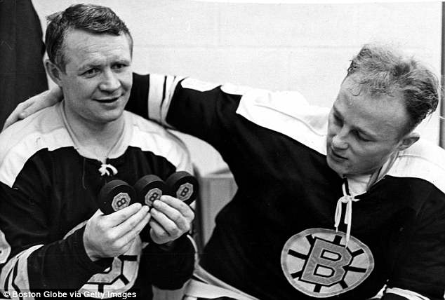 Boston Bruins player McKenzie, left, holds up three pucks after scoring three goals in a game against the Detroit Red Wings at the Boston Garden on Feb. 4, 1968