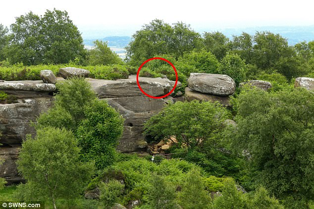 The rock was toppled from the circled spot to the ground below, leaving the site damaged as youths also carved their names into the surface