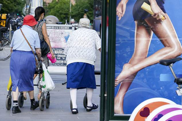 New rules: Members of the public are seen walking past a billboard in Sweden