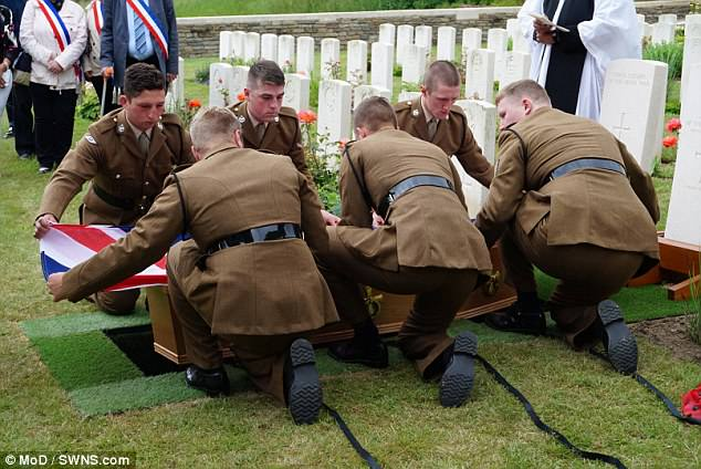 Royal Tank Regiment soldiers lower their colleagues coffin theLoos British Cemetery in France